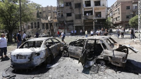 Charred vehicles are seen at the site of a suicide bomb attack in the Syrian capital's eastern Tahrir Square district.