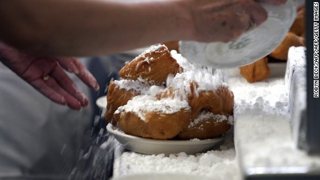 Waitresses prepare beignets by covering them with powdered sugar in the kitchen of Cafe du Monde.