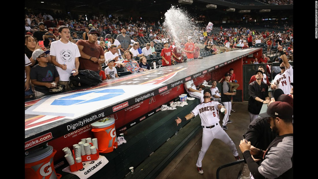 Arizona's David Peralta playfully throws water from the dugout in Phoenix before the start of a game on Wednesday, June 28.