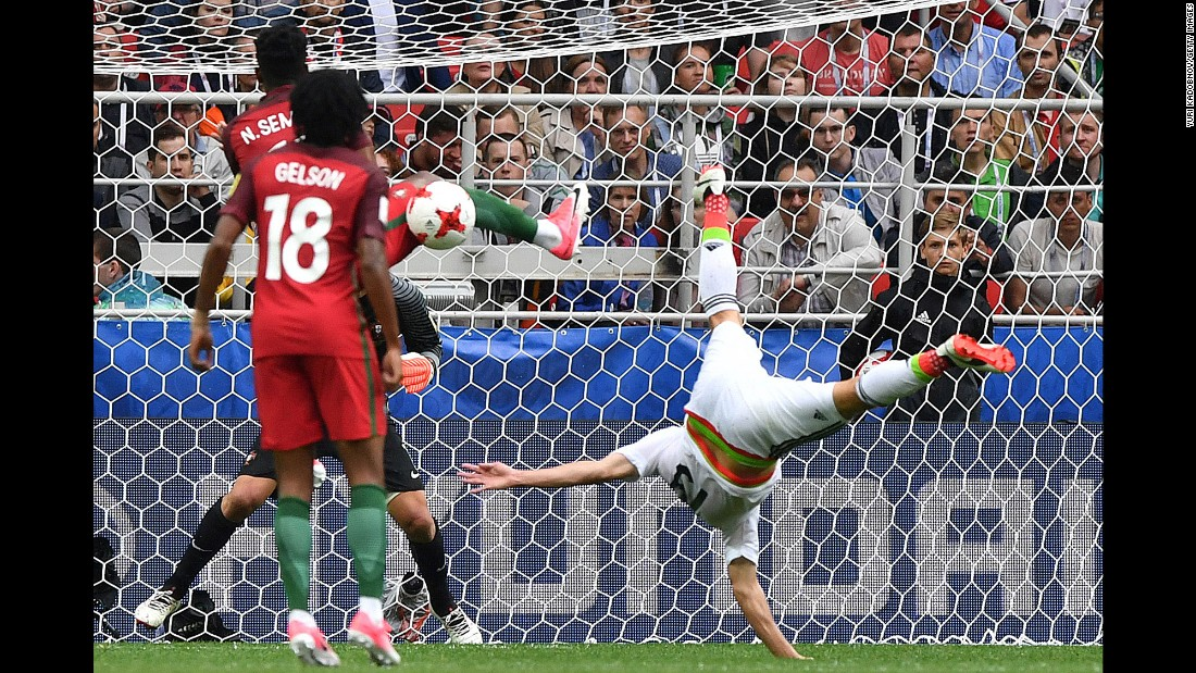 Mexican forward Oribe Peralta falls over as his shot is blocked by Portugal's Nelson Semedo on Sunday, July 2. Portugal won 2-1 to claim third place in the Confederations Cup.