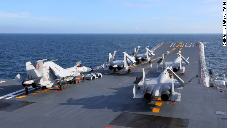 The J-15 fighter jets sit on the flight deck of the aircraft carrier Liaoning prior to a training exercise on July 1.