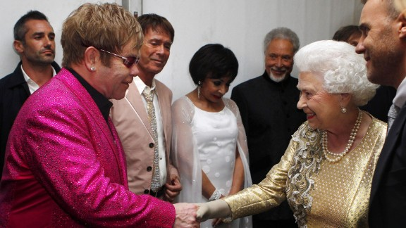 Britain's Queen Elizabeth II shakes hands with John at her Diamond Jubilee Concert in 2012. In 1998, the Queen knighted John for his music and charity work.