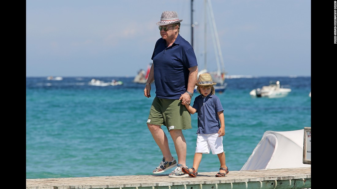 John walks with his son Zachary in Saint-Tropez, France, in 2015.