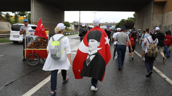 Justice March participant draped in flag with the Turkey's founder Mustafa Kemal Ataturk on it.