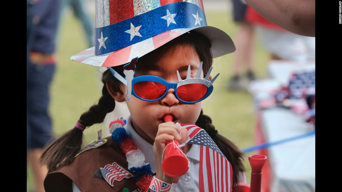 Girl Scout Hana Cho tests out a horn prior to a July Fourth parade in Santa Monica, California.