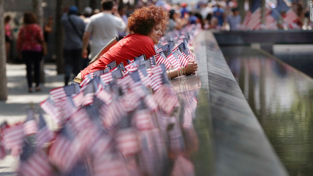 A woman pauses among American flags that were planted at the reflecting pools of the 9/11 Memorial in New York.