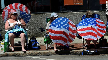 Bearing patriotic parasols, Marilyn Barrows of Framingham, Mass., left, and other parade-goers follow the 62nd Annual 4th of July Parade in Natick, Mass., Tuesday, July 4, 2017. (Ken McGagh/The Metro West Daily News via AP)