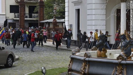 Supporters of Venezuelan President Nicolas Maduro storm the National Assembly building in Caracas on July 5, 2017 as opposition deputies hold a special session on Independence Day. A political and economic crisis in the oil-producing country has spawned often violent demonstrations by protesters demanding President Nicolas Maduro's resignation and new elections. The unrest has left 91 people dead since April 1. / AFP PHOTO / Juan BARRETO        (Photo credit should read JUAN BARRETO/AFP/Getty Images)