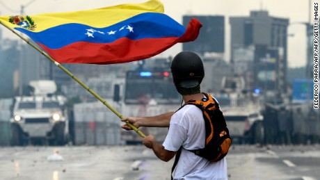 A Venezuelan opposition demonstrator waves a flag during a protest in May.