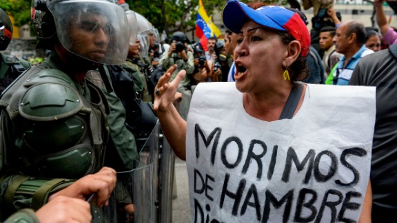 "TOPSHOT - A woman with a sign reading ""We starve"" protests against new emergency powers decreed this week by President Nicolas Maduro in front of a line of riot policemen in Caracas on May 18, 2016.  Public outrage was expected to spill onto the streets of Venezuela Wednesday, with planned nationwide protests marking a new low point in Maduro's unpopular rule. / AFP / FEDERICO PARRA        (Photo credit should read FEDERICO PARRA/AFP/Getty Images)"