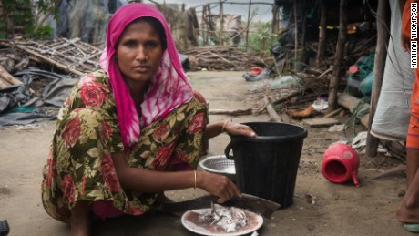 Hasna Akter prepares fish to feed her family in a rented shack in Cox's Bazar, Bangaldesh.