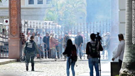 Supporters of Venezuelan President Nicolas Maduro stand at the gate of the National Assembly building in Caracas before storming it on July 5, 2017 as opposition deputies hold a special session on Independence Day. A political and economic crisis in the oil-producing country has spawned often violent demonstrations by protesters demanding President Nicolas Maduro's resignation and new elections. The unrest has left 91 people dead since April 1. / AFP PHOTO / Juan BARRETO        (Photo credit should read JUAN BARRETO/AFP/Getty Images)