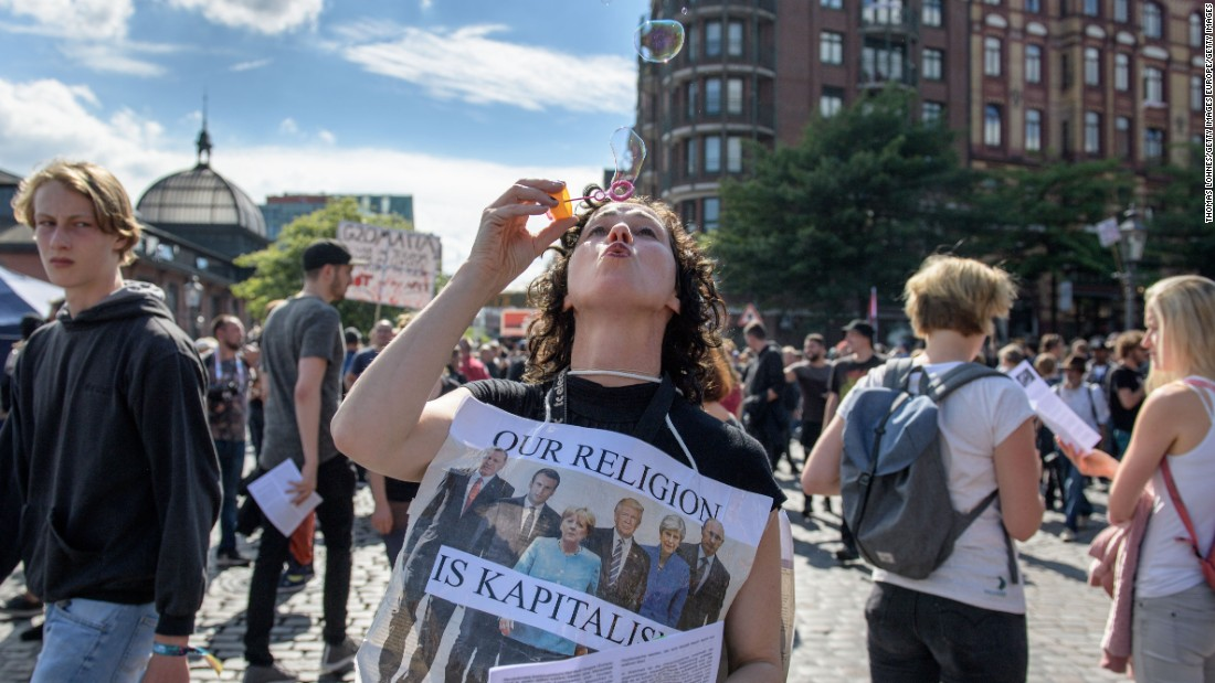 A woman wearing a sign depicting the G20 summit world leaders blows bubbles at Hamburg harbor before the protest march.