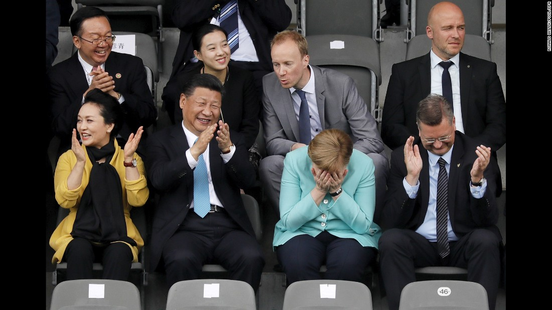 German Chancellor Angela Merkel puts her head in her hands as she watches a youth soccer game in Berlin with Chinese President Xi Jinping and his wife, Peng Liyuan, on Wednesday, July 5. The game was played between the under-12 teams of Germany and China.