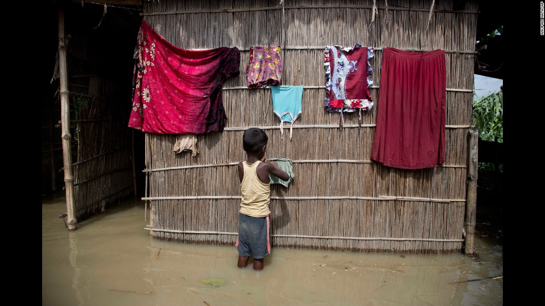 A boy dries clothes outside his house, which was partially submerged in floodwaters in Burgaon, India, on Wednesday, July 5. Heavy rains have triggered floods and landslides in parts of the country's remote northeast.