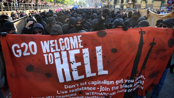 "HAMBURG, GERMANY - JULY 06:  Protesters  dressed in all black hold up a banner as they take part in the ""Welcome to Hell"" protest march on July 6, 2017 in Hamburg, Germany.  Leaders of the G20 group of nations are arriving in Hamburg today for the July 7-8 economic summit and authorities are bracing for large-scale and disruptive protest efforts tonight at the ""Welcome to Hell"" anti-G20 protest.  (Photo by Leon Neal/Getty Images)"