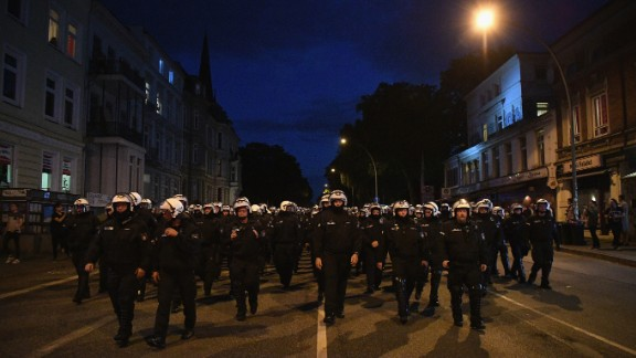 "Riot police head down a road during the ""Welcome to Hell"" protest march on Thursday, July 6."