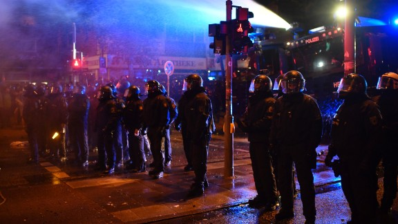 Police stand guard in the street while protesters erect barricades July 7 in Hamburg.