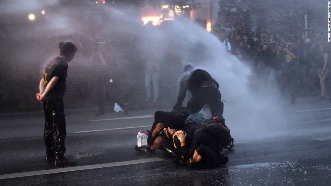 Riot police use a water cannon on demonstrators.
