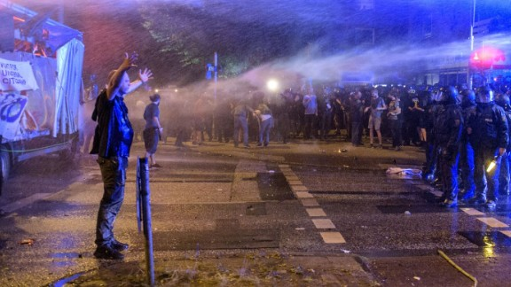 A demonstrator is sprayed by water canons.