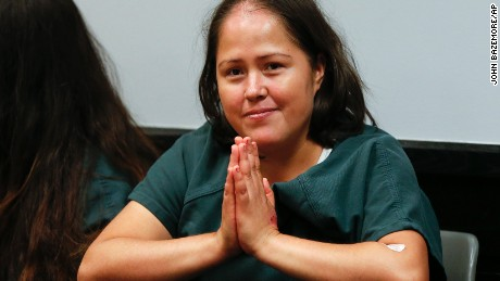 A smiling Martinez holds her hands together as if in prayer Friday in court.