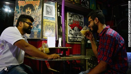 Indian men drink coffee from beer mugs at Pecos, one of Bangalore's oldest pubs.