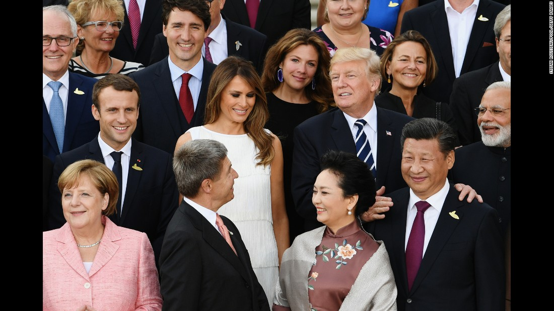 Trump joins world leaders and their partners as they pose for photos before the concert.