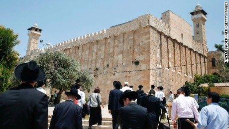 A picture taken on July 7, 2017 shows religious Jews and tourists walking towards the Cave of the Patriarchs, also known as the Ibrahimi Mosque.