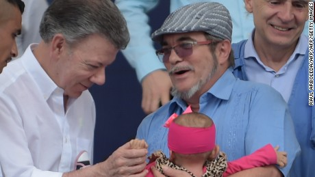 "FARC rebel leader Rodrigo Londono Echeverri, known as ""Timochenko""(C) holds a baby, next to Colombian President Juan Manuel Santos (2-L), the UN Secretary-General's Special Representative for Colombia and Head of the UN Mission to Colombia, Jean Arnault (2-R) and two FARC members during the final act of abandonment of arms and the FARC's end as an armed group at Transitional Standardization Zone Mariana Paez, Buena Vista, Mesetas municipality, Colombia on June 27, 2017. / AFP PHOTO / RAUL ARBOLEDA        (Photo credit should read RAUL ARBOLEDA/AFP/Getty Images)"