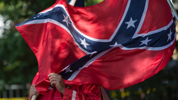 A member of the Ku Klux Klan holds a Confederate flag over his face during a rally, calling for the protection of Southern Confederate monuments, in Charlottesville, Virginia on July 8, 2017. The afternoon rally in this quiet university town has been authorized by officials in Virginia and stirred heated debate in America, where critics say the far right has been energized by Donald Trump's election to the presidency.  / AFP PHOTO / ANDREW CABALLERO-REYNOLDS        (Photo credit should read ANDREW CABALLERO-REYNOLDS/AFP/Getty Images)