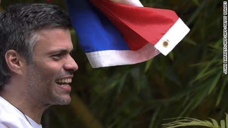 "Venezuelan opposition leader Leopoldo Lopez displays a Venezuelan national flag as he greets supporters gathering outside his house in Caracas, after he was released from prison and placed under house arrest for health reasons, on July 8, 2017. Venezuela's Supreme Court confirmed on its Twitter account it had ordered Lopez to be moved to house arrest, calling it a ""humanitarian measure"" granted on July 7 by the court's president Maikel Moreno. ""Leopoldo Lopez is at his home in Caracas with (wife) Lilian and his children,"" Lopez's Spanish lawyer Javier Cremades said in Madrid. ""He is not yet free but under house arrest. He was released at dawn."" / AFP PHOTO / Juan BARRETO        (Photo credit should read JUAN BARRETO/AFP/Getty Images)"
