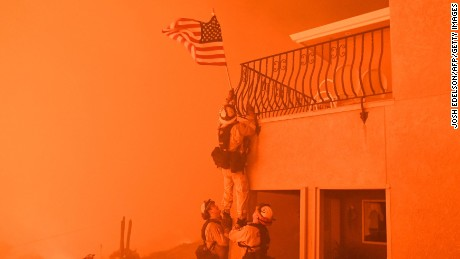 "Firefighters remove a US flag as flames from the ""Wall Fire"" close in on a luxury home in Oroville, California over the weekend."