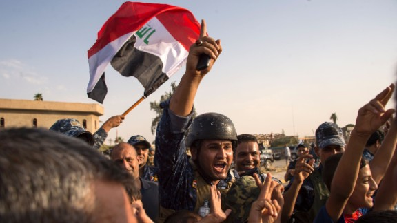 Members of the Iraqi federal police wave the country's flag as they celebrate in the Old City of Mosul on July 9, 2017. Iraq declared victory against ISIS forces in Mosul after a grueling monthslong campaign. The battle to reclaim Mosul, the last major ISIS stronghold in Iraq, has been underway since fall 2016.