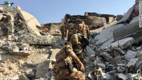 Counter Terror Service (CTS) Troops climb a mound of rubble to reach a house turned fighting position just 50 meters from the Tigris river. They are engaged in fierce clashes to push out ISIS's remaining pockets of resistance.