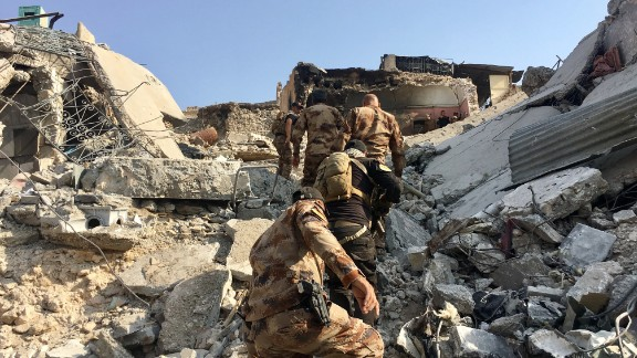 Counter Terror Service (CTS) Troops climb a mound of rubble to reach a house turned fighting position just 50 meters from the Tigris river. They are engaged in fierce clashes to push out ISIS