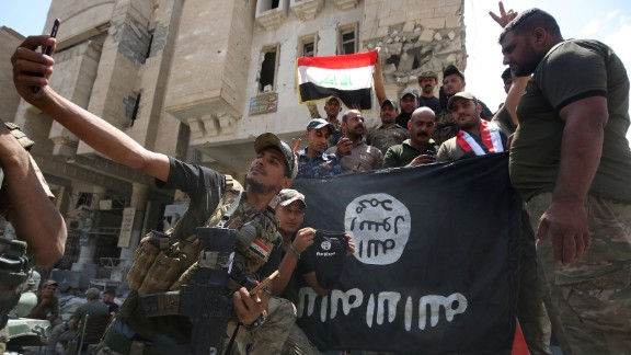 Members of the Iraqi interior ministry forces pose for a picture with an upside down Islamic State (IS) group flag in the Old City of Mosul on July 8, 2017, as their part of the battle has been declared accomplished, while other forces continue to fight the jihadists in the city.  AHMAD AL-RUBAYE/AFP/Getty Images