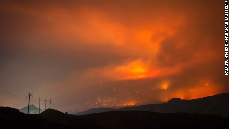 A wildfire burns on a mountain in the distance east of Cache Creek, British Columbia, Canada in the early morning hours of Monday July 10, 2017.
