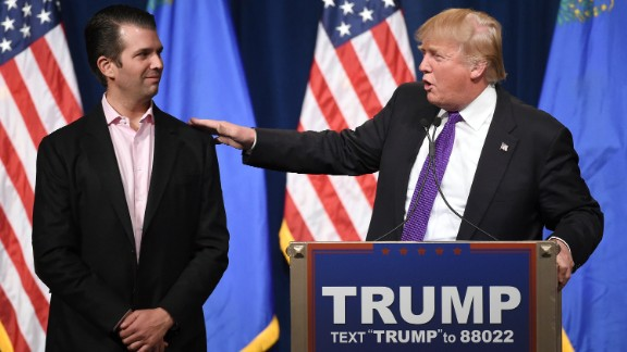 """LAS VEGAS, NV - FEBRUARY 23:  Donald Trump Jr. (L) looks on as his father, Republican presidential candidate Donald Trump, speaks at a caucus night watch party at the Treasure Island Hotel & Casino on February 23, 2016 in Las Vegas, Nevada. The New York businessman won his third state victory in a row in the """"first in the West"""" caucuses.  (Photo by Ethan Miller/Getty Images)"""