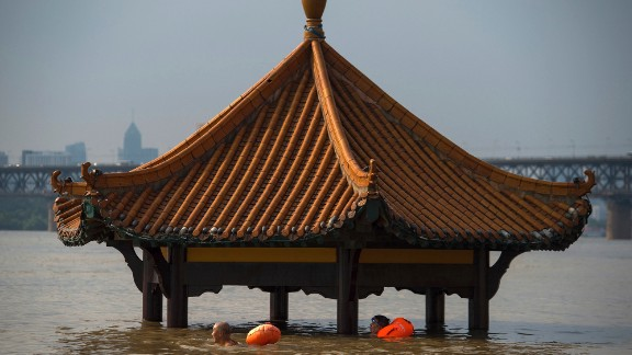 People swim past the top of a pagoda at a flooded riverside park in Wuhan in central China