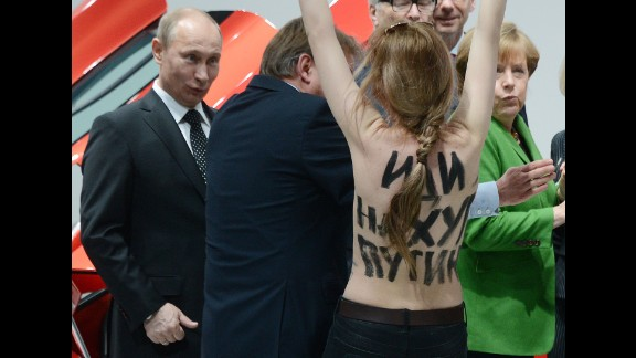 """A topless protester shouts at Putin and German Chancellor Angela Merkel during a visit to central Germany in April 2013. That month, Putin defended his government's record on free speech and rejected a claim that it uses """"Stalinist"""" methods to clamp down on critics and activists. Two international rights groups had issued scathing reports on Putin's presidency, saying changes to the law had helped authorities stifle dissent."""