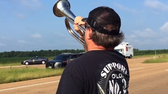 David Weeks, of Inverness, Mississippi, plays taps Tuesday near the crash site.