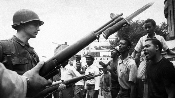 National Guardsmen try to ignore heckling of protestors on Newark's Springfield Ave. as violence continued into a third day. Eleven died and hundreds were injured during the riots.