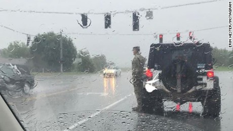 A soldier was recently captured standing at attention in the rain outside his vehicle during a funeral procession in Vine Grove, Kentucky.