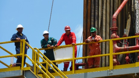 Workers tand on the deck of an oil well operated by Venezuela's state-owned oil company PDVSA in Morichal, Venezuela, on July 28, 2011. Venezuela will fulfill its compromise of co-financing with its Brazilian counterpart Petrobras the construction of the Abreu y Lima oil refinery that would process 240,000 oil drums per day, venezuela's Oil and Energy Minister Rafael Ramirez said on July 29, 2011.   AFP PHOTO/Ramon SAHMKOW (Photo credit should read RAMON SAHMKOW/AFP/Getty Images)