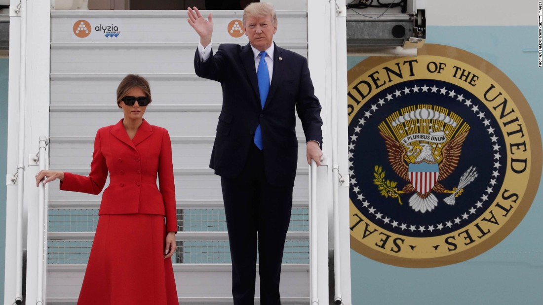 President Trump waves as he and his wife arrive at Paris' Orly Airport.