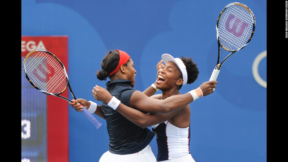 Venus and Serena celebrate winning a gold medal together at the 2008 Beijing Olympics.