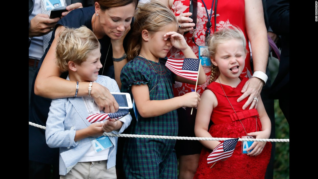 Children react to the rotor wash of the President's helicopter as it lands at the White House on Wednesday, July 12.