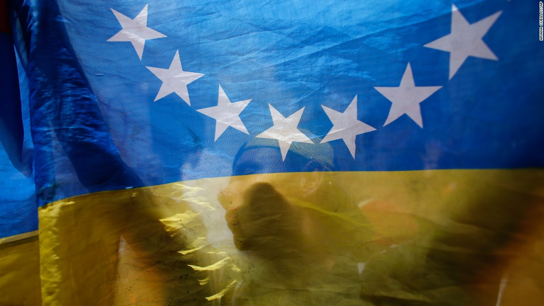 "An anti-government demonstrator is seen behind a Venezuelan flag during a protest in Caracas, Venezuela, on Sunday, July 9. Venezuela <a href=""http://www.cnn.com/2017/04/12/world/gallery/venezuela-protests/index.html"" target=""_blank"">has seen widespread unrest</a> since March 29, when the Supreme Court dissolved Parliament and transferred all legislative powers to itself. The decision was later reversed, but protests have continued across the country."