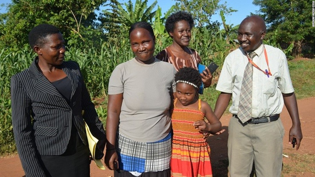 "Wells and her husband discovered the truth when they found a Facebook page for Reunite and saw a photo of a woman who claimed that her children had been taken. ""We said, 'that's Violah's mother,' "" Wells said. ""And we were just sick."" Here, Ugandan investigators join Violah and her mother (center, in gray shirt) for the reunion.<br />"