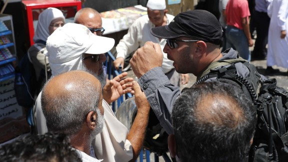 An Israeli security forces member argues Friday with Palestinians outside Jerusalem's Damascus Gate.
